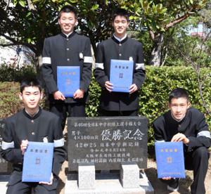 吉田中の卒業式で日本新の記念碑の前でポーズをとるリレーメンバーの(左から)斉藤、田村、内屋、大石