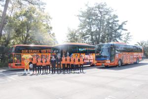 応援バス(中央と右)の披露会に参加した山室社長(右から6人目)と選手たち(カメラ・山田 豊)