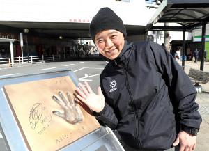 大和駅前に設置された自身の手形モニュメントの前でポーズする