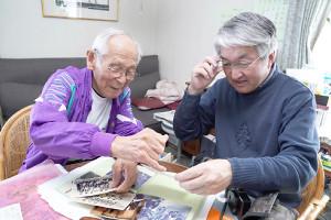 夏苅さん(左)が大事に保存している実父・田中さんの写真を見つめる黒木さん(カメラ・矢口 亨)