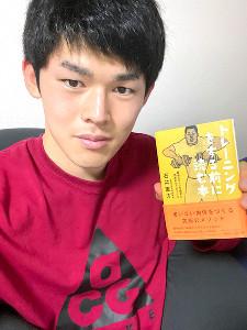 最近読んだトレーニングに関する 本を持つ佐々木朗希(球団提供)