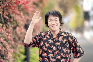 「94歳の母の手作り」というカニ柄のシャツを着てポーズを決める河崎実監督(カメラ・矢口 亨)