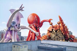 「三大怪獣グルメ」に登場する(左から)イカラ、タッコラ、カニーラとチラシ(下)