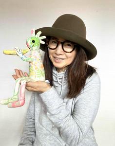 自ら絵を描いたココペリの人形を手にほほ笑む風吹ジュン(本人提供)