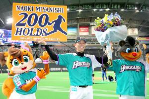 日本ハム・宮西が通算200ホールドを達成し、ボードを掲げて笑顔