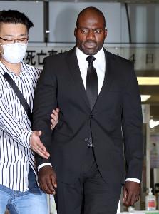 マネジャーに手を取られながらスーツ姿で釈放されたボビー容疑者