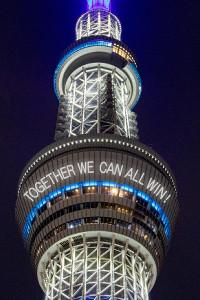 地球をイメージした青色の特別ライティングと、天望デッキにレーザーマッピングで投影される「TOGETHER WE CAN ALL WIN!」のメッセージ(イメージ)(C)TOKYO SKYTREE