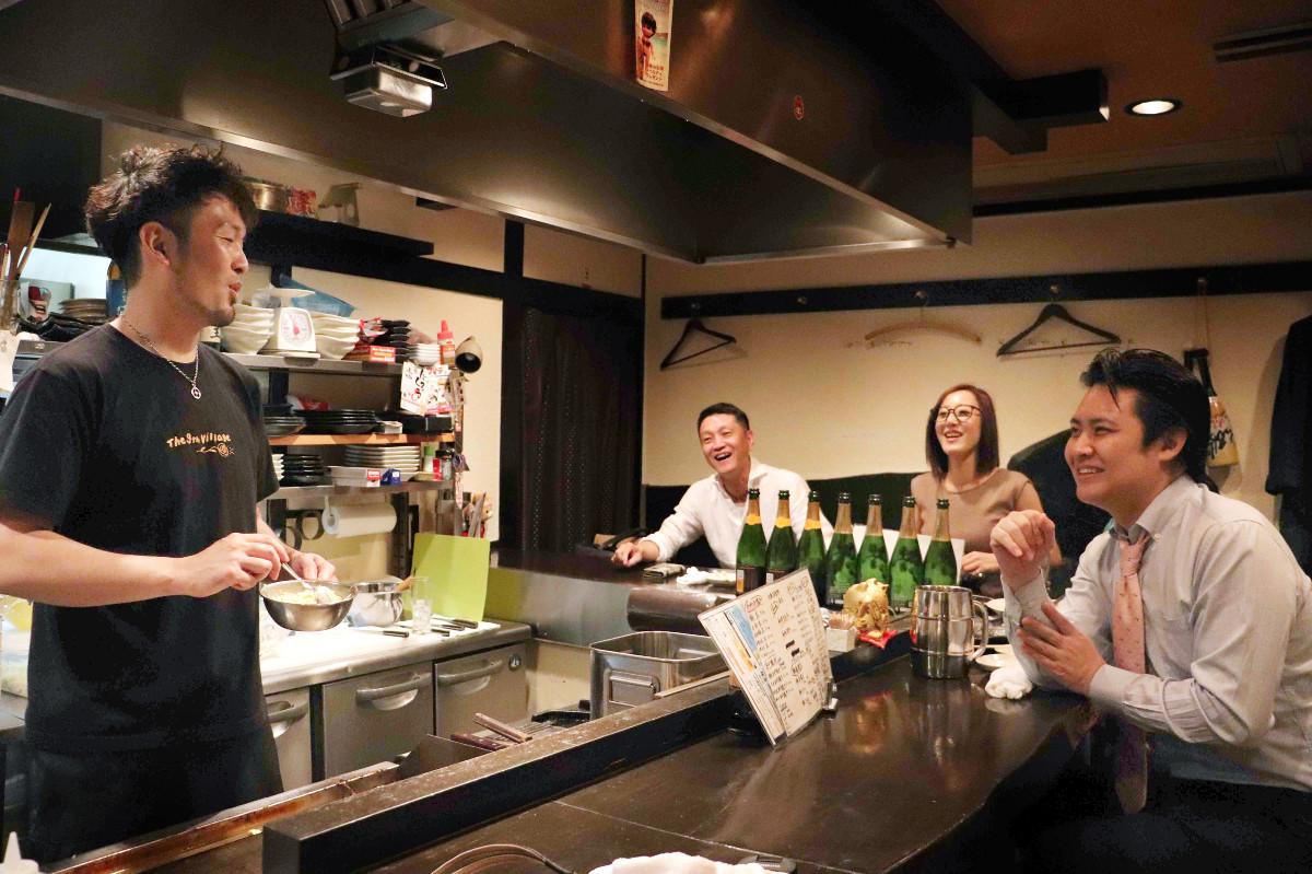 お好み鉄板酒場「どら十」でコテを握る元阪神打撃投手の水落暢明さん(左端)が常連客と談笑する(カメラ・古田 尚)