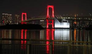 午後11時過ぎ、赤色にライトアップされたレインボーブリッジ。新型コロナの感染再拡大により「東京アラート」が発令された