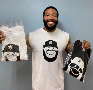 「Smiley J Tシャツ」を手にジャクソンスマイルを見せるロッテのジャクソン=球団提供