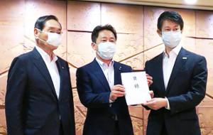 広島県庁で湯崎英彦広島県知事(右)に目録を贈呈した松本太郎企業長(中)と入山欣郎副企業長(左)