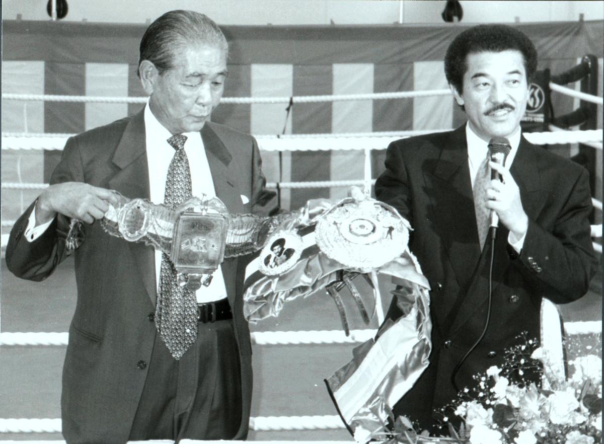 95年9月、「白井・具志堅スポーツジム」の開館発表会でお互いのチャンピオンベルトを見せる白井義男さん(左)と具志堅会長