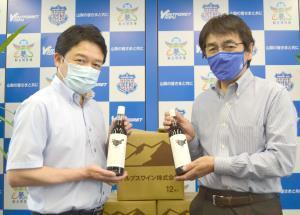 「ヨゲンノトリラベル」を手にするアルプスワイン・前島取締役総括部長(左)と甲府・藤原社長