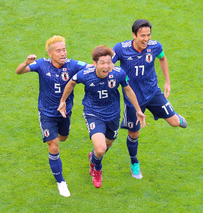 日本・コロンビア戦で勝ち越しゴールを決め、日本ベンチへ向かう大迫勇也(左は長友佑都、右は長谷部誠)