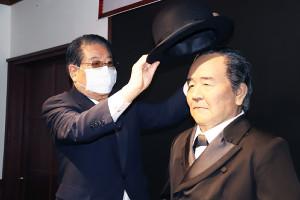渋沢栄一アンドロイド(右)に帽子をかぶせるドトールコーヒー鳥羽博道会長