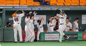 8回無死、右越えソロ本塁打を放った丸佳浩(右)はベンチ前でウィーラー(左)らに「マルポーズ」で迎えられる(カメラ・竜田 卓)