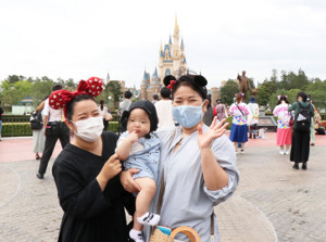 東京ディズニーランドを訪れた親子連れは、シンデレラ城をバックに笑顔