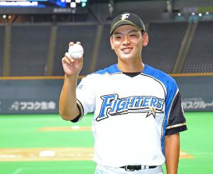 2日の試合後、プロ初本塁打の記念球を手に笑顔を見せる野村