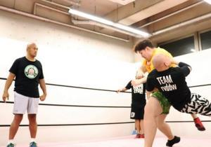 タックルの練習をする納谷幸男にアドバイスを送る秋山準(左)