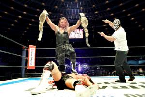 12日の2冠戦で内藤哲也を撃破、IWGPヘビー、インターコンチネンタルの2つのベルトを掲げるEVIL(右はマスクを着けたディック東郷=新日本プロレス提供)