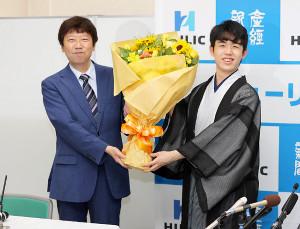師匠の杉本昌隆八段(左)から花束を受け取り、満面の笑みを見せた藤井聡太新棋聖