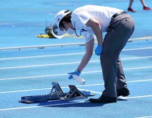 東京選手権のスタッフがスターティングブロックを消毒