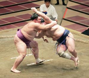 朝乃山(左)はすくい投げで北勝富士を下す