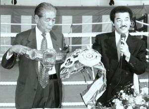1995年9月の白井具志堅スポーツジムの開館発表会で、互いのチャンピオンベルトを見せる白井義男さん(左)と具志堅用高会長