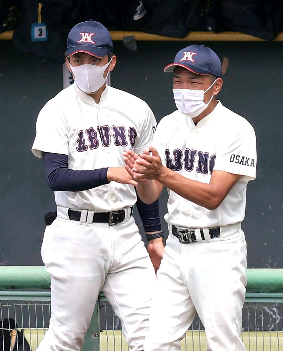 試合に勝利し、拍手で迎える阿武野・大辻民基監督(右)と筒井大樹部長