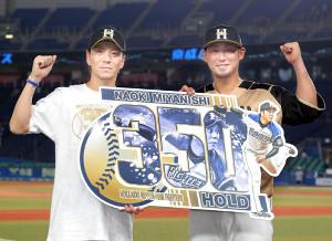 通算350ホールドを達成し、中田(右)と記念ボードを持つ宮西