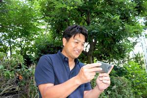 屋外でスマホでDAZNを楽しむ高橋由伸さん
