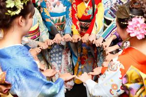 手をつなぐ着物姿のモデルたち。鮮やか色彩とともに「世界はきっと、ひとつなれる。」のメッセージを発信している