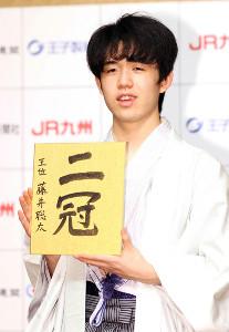 二冠と書かれた色紙を手に笑顔を見せる藤井聡太新王位