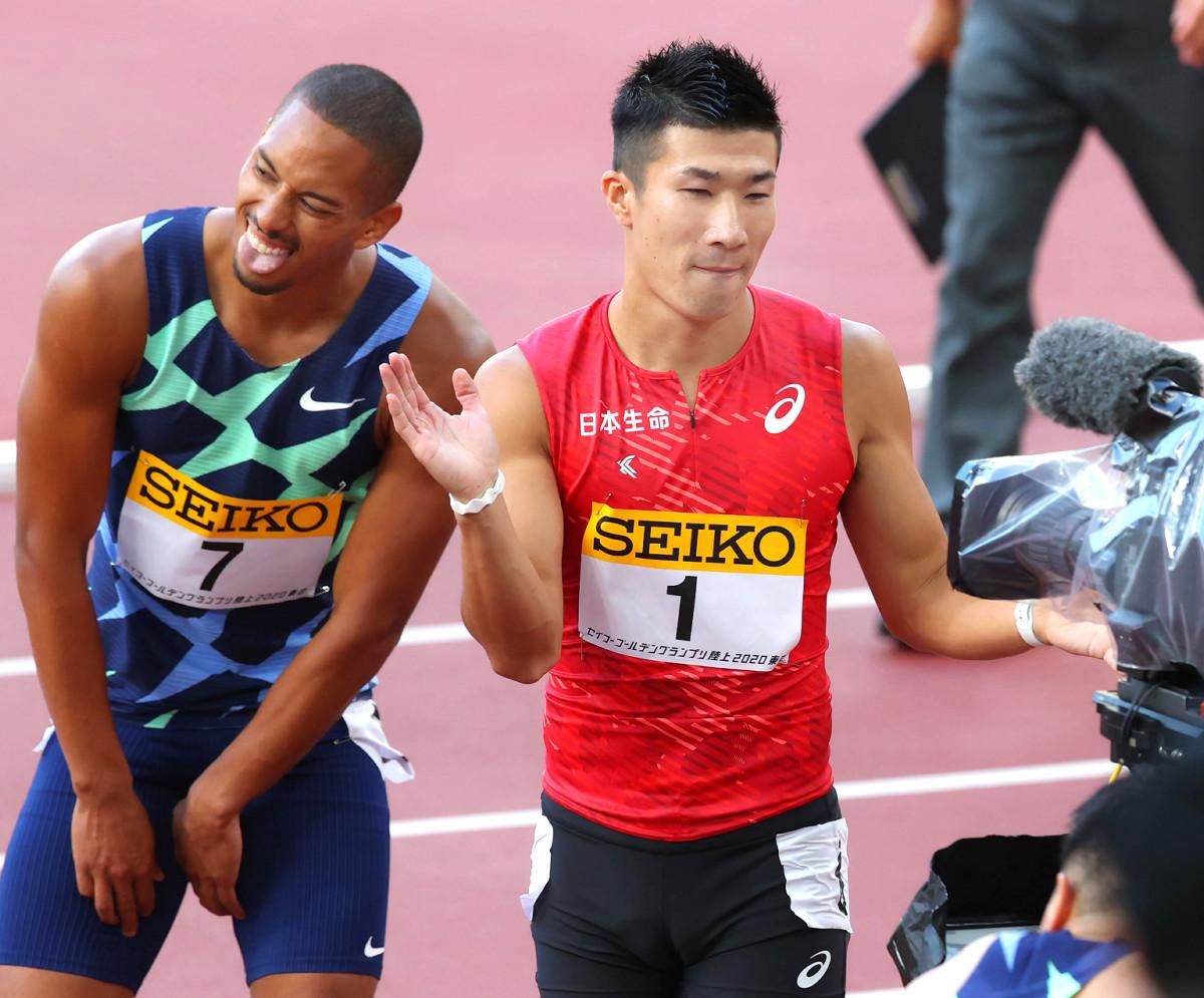 優勝した桐生(右)は2位で悔しがるケンブリッジの横でテレビカメラに向かって手を叩いて見せる