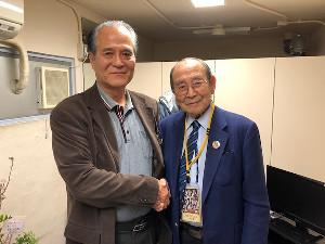 新間寿氏(右)と握手する山崎照朝氏