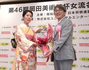 祝賀パーティーでゲストとして登場した羽生善治九段(右)から花束を贈られる里見香奈女流名人