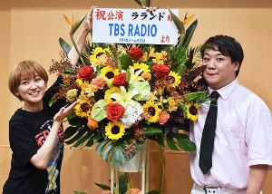 TBSラジオから贈られた花を囲んで記念撮影をするラランド・サーヤ(左)とニシダ