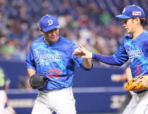 7回の投球を終えて、京田陽太(右)とタッチを交わす大野雄大