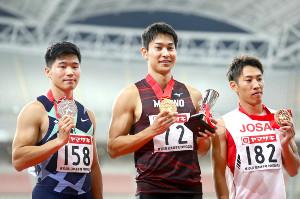 表彰式で笑顔を見せる飯塚(左は小池、右は鈴木)