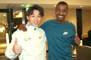 チームメートとなる3月の東京マラソン2位のバシル・アブディ(右)と肩を組む福田穣