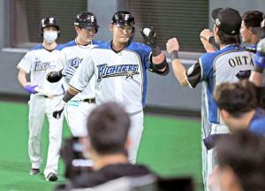 9回に意地の2ランを放ちナインに迎えられる中田(手前左)