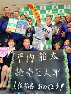 巨人からドラフト1位指名を受け、仲間の祝福を受けながら投球フォームを披露する亜大・平内龍太(中央)
