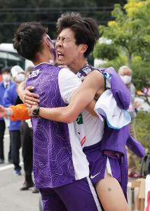 優勝のゴールテープを切り、チームメイトに抱きつく駒大・田沢廉