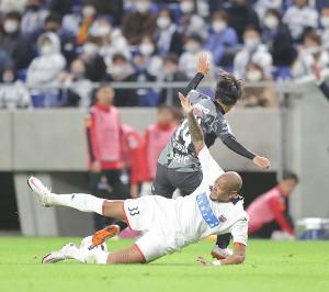 前半43分、G大阪・福田湧矢(奥)に倒される札幌・ドウグラス・オリヴェイラ