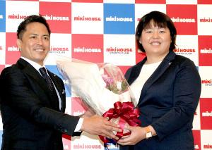 ミキハウス本社で引退会見を行った山部佳苗(右)は野村忠宏GMから花束を贈られて笑顔