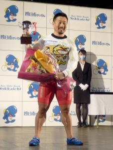 優勝カップと花束を手に満面の笑みを浮かべる佐藤慎太郎