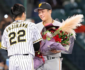 藤川(左)に花束を渡してねぎらう坂本