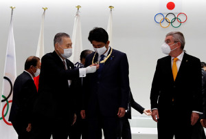 安倍前首相(中)の首にかけられた「五輪オーダー」の記念品を見る東京五輪・パラリンピック組織委の森会長。右はIOC・バッハ会長(ロイター)