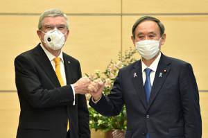 首相官邸を訪れ、菅首相(右)の歓迎を受けるバッハ会長(ロイター)