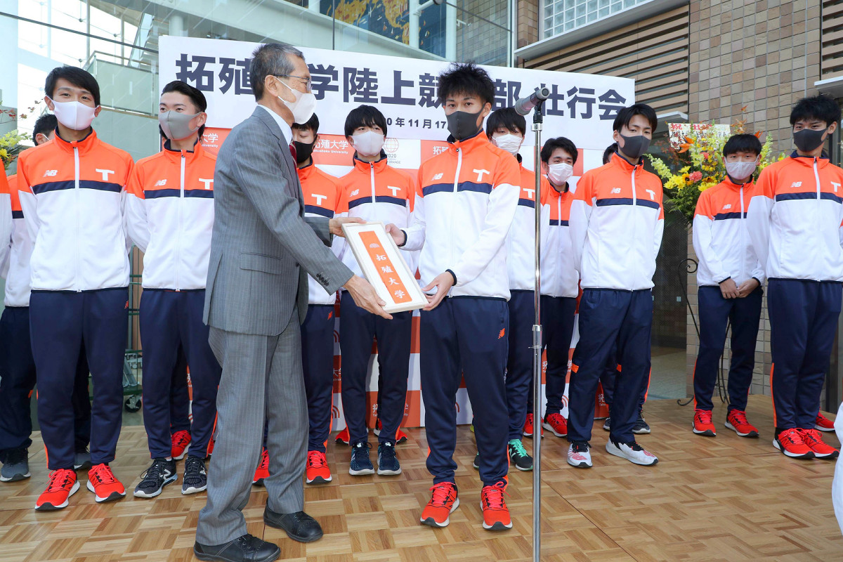 壮行会で、川名明夫・拓大学長(左)からタスキを受け取る石川佳樹・陸上競技部主将